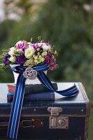 Romantic flower arrangement and antiquarian books on vintage suitcase decorated with elegant ribbon and brooch