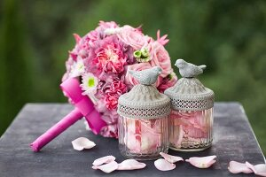 Romantic bridal bouquet with pink roses, scattered rose petals and glass jars with bird figurines on lids