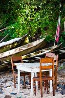 Tisch und Stühle am Strand neben alten Holzbooten