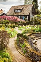 Paved path leading between flowerbeds in spring garden to wooden house