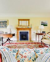 View over sofa to open fireplace flanked by antique tables in rustic, traditional, elegant living room