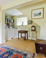 Fitted cabinets and antique furniture in yellow-painted niche under staircase