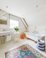 Colourful rug on white wooden floor in rustic wood-clad bathroom