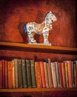 Antique ceramic horse on bookshelf