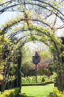 Climber-covered trellis arches framing dovecot in spring garden