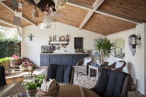 Comfortable wicker furniture on vintage-style roofed terrace