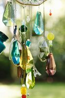 Glittering crystal pendants and beads hanging from hand-crafted wind chimes in garden
