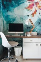 Retro swivel chair at modern desk against wall with floral motif