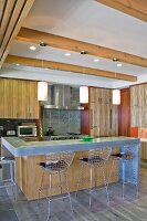 Metal barstools at counter below pendant lamps hanging from wood-beamed ceiling in open-plan kitchen