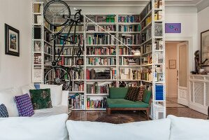 Industrial-style bookcase used as partition around reading corner with vertical bike-rack