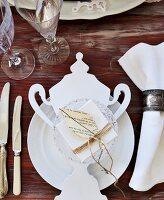 Weisses Gedeck mit nostalgischer Papierdeko auf Holztisch