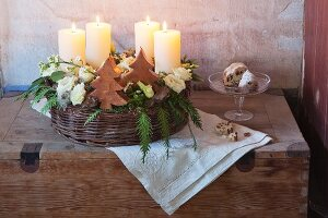 A woven basket with advent candles, Japanese roses, coral roses and conifer sprigs
