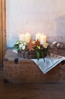 A woven basket with advent candles, Japanese roses, coral roses and conifer sprigs decorated for Christmas in a vintage wooden chest