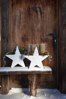 Advent arrangement of pine branches and silver wire on white china stars on snowy wooden bench