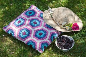 Romantic sun hat on crocheted cushion with blue and purple Granny-style hexagon pattern next to bowl of blackberries