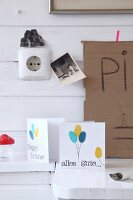 Hand-crafted birthday cards with balloon motifs below black and white photos on white wooden wall