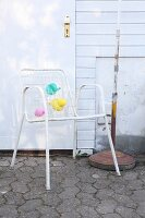 White lattice garden chair decorated with pastel balloons