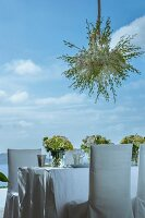 Wedding dinner table festively set with vases of flowers and upholstered chairs with white loose covers outdoors