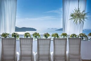 Chairs with white loose covers around festively set wedding dinner table with sea view
