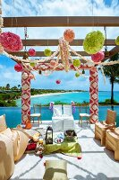 Indian wedding - chairs with white and gold loose covers below pergola decorated with flowers next to ocean
