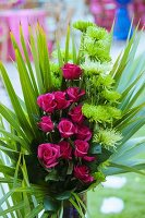 Festive arrangement of pink roses wrapped in palm fronds