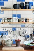 Shelves of spices and crockery above cooking utensils hung from stainless steel rod on kitchen wall with white and blue tiles