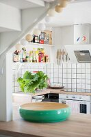 Green bamboo bowl on counter in front of L-shaped kitchen counter with white-tiled splashback