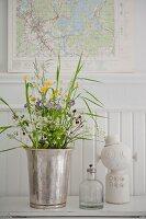 Wiesenblumenstrauß in Silbervase mit Öllämpchen und Dekofigur vor schwedischer Landkarte