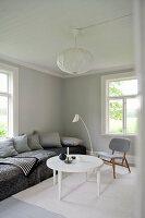 Weisser, runder Couchtisch und gemütliches Polstersofa in Wohnzimmerecke in minimalistisch, skandinavischem Flair