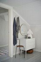 Vintage Hocker und weisse Schubladenkommode in Zimmerecke vor Dachschräge