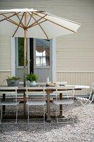 Sitzplatz unter Sonnenschirm auf gekiester Terrassen vor Holzhaus