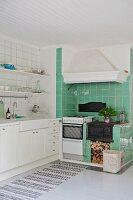 Küchenzeile mit weissen Unterschränken und grün gefliester Kochbereich mit gusseisernem Ofen und Dunstabzug