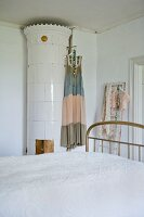 Summer dress hung on antique, white, cylindrical tiled stove