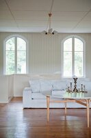 Round coffee table in front of white sofa and arched windows