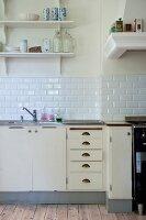 Vintage kitchen counter with base units below white-tiled splashback