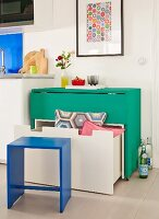 A white bench with a drawer under a folding green table with wheels; storage solutions with space saving furniture