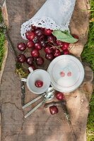 Crockery printed with cherry pattern and paper cone of cherries