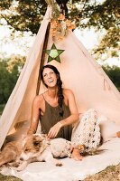 Laughing woman and dog sitting in decorated teepee