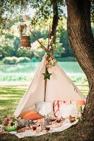 Romantic picnic in open-fronted teepee under tree in idyllic summer landscape
