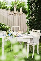 Chandelier above romantic coffee table set with blue flowers in garden