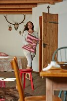 Woman carrying red and white gingham cushion in rustic bedroom with antlers above bed