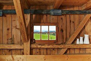 Kleines Sprossenfenster zwischen der Tragkonstruktion einer rustikalen Holzwand, Sammlung weisser Kannen auf einem Balken