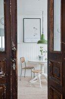 Blick durch eine alte Kassettentür auf einen runden Tisch