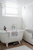 Nostalgisches Badezimmer mit freistehender Wanne und Bretterwand
