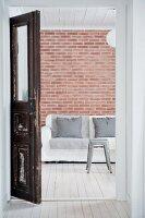 Blick durch eine alte Holztür auf ein Sofa vor Backsteinwand