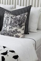 Black and white patterned scatter cushions arranged on bed