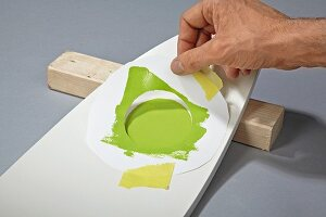Revamping a chair backrest with green paint and circular stencil