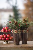 Two small metal buckets decorated with vintage ribbons, spruce twigs and pine cones in front of red apples on cake stand