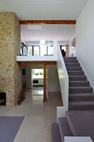 Staircase with light grey carpet leading to gallery in open-plan luxury interior