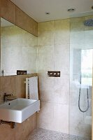 Corner of elegant bathroom with large wall tiles and glazed shower area